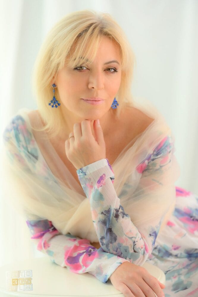 Fotografie facuta la o sedinta foto glamour pentru femei, reprezentand o femeie blonda cu rochie crem cu imprimeuri, cercei albastri, pe fundal alb